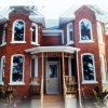 traditional red brick home with new curve top windows